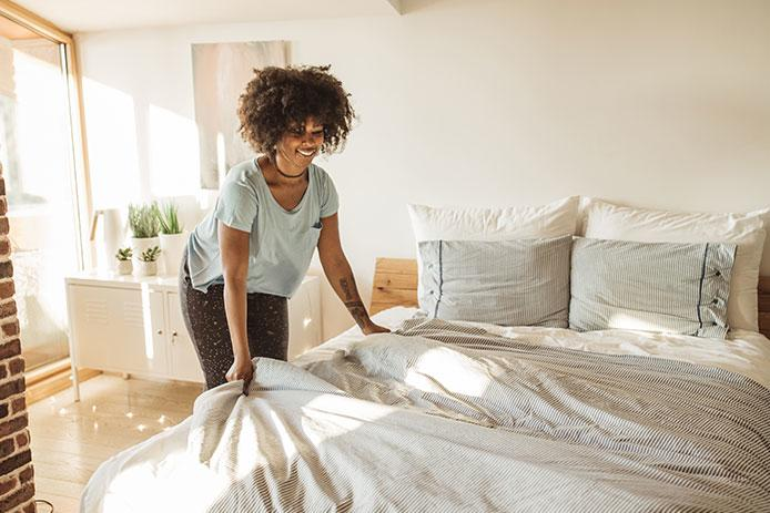 Woman changing linens on guest bed